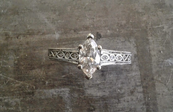 intricate filigree white gold band with delicate marquise cut diamond in cathedral setting engagement ring top view