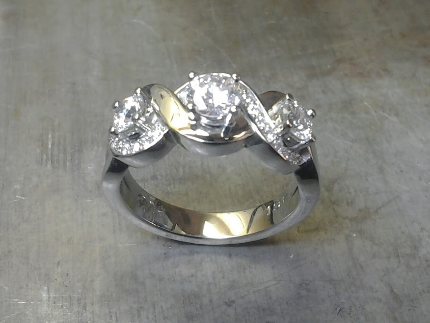 custom designed white gold engagement ring with swirled band and triple set diamonds