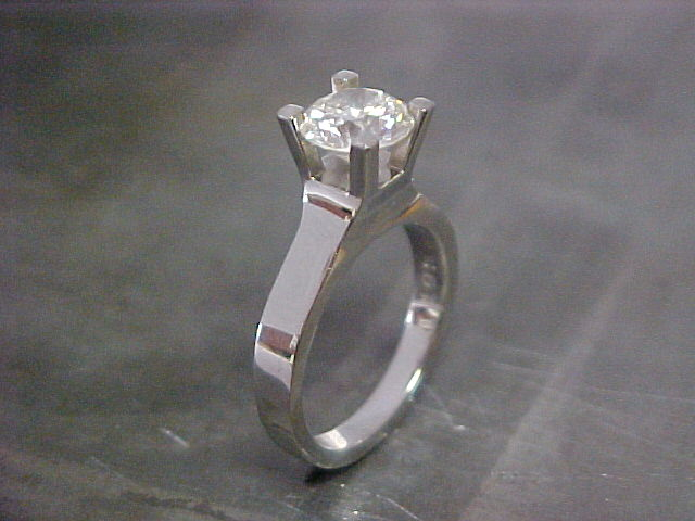 slim white gold band with large center diamond in deep cathedral setting