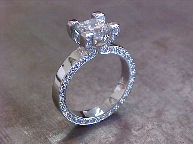 custom designed diamond band engagement ring with princess cut diamond in channel setting