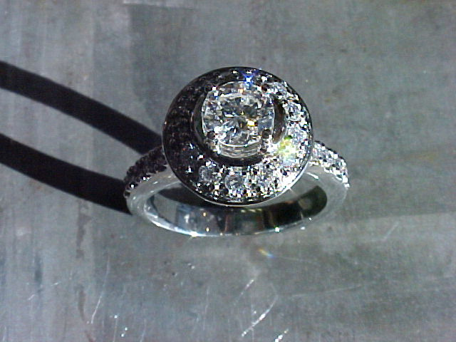 custom engagement ring with large round diamond in halo setting and diamond encrusted band