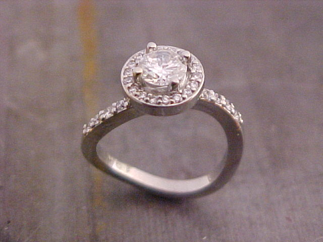 custom engagement ring with unique band shape and halo set round diamond
