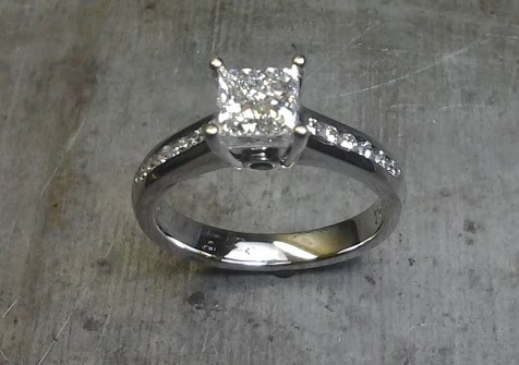 Princess cut engagement ring with sapphire in side and diamonds down shank
