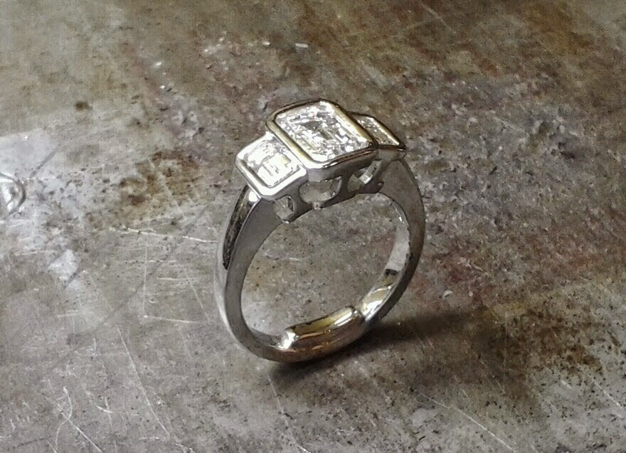 3 stone emerald cut bezel engagement ring
