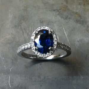 Top View Royal Blue Sapphire set in 19k white gold with diamond set halo and sides