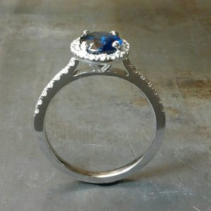 Finger through view Royal Blue Sapphire set in 19k white gold with diamond set halo and sides