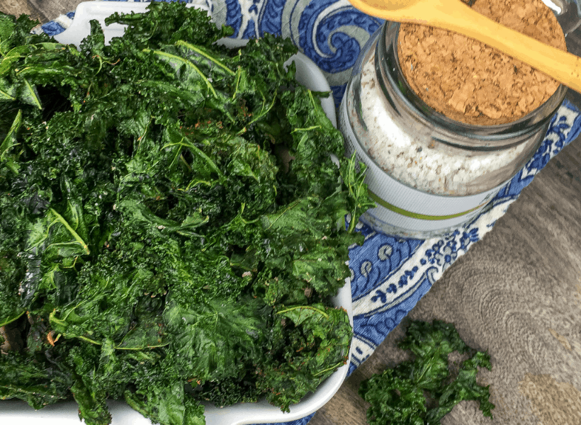 bowl of crispy kale chips with seasoning after baked in oven