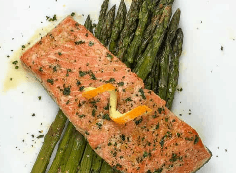 salmon with orange glaze and garnish on top of asparagus on a white plate