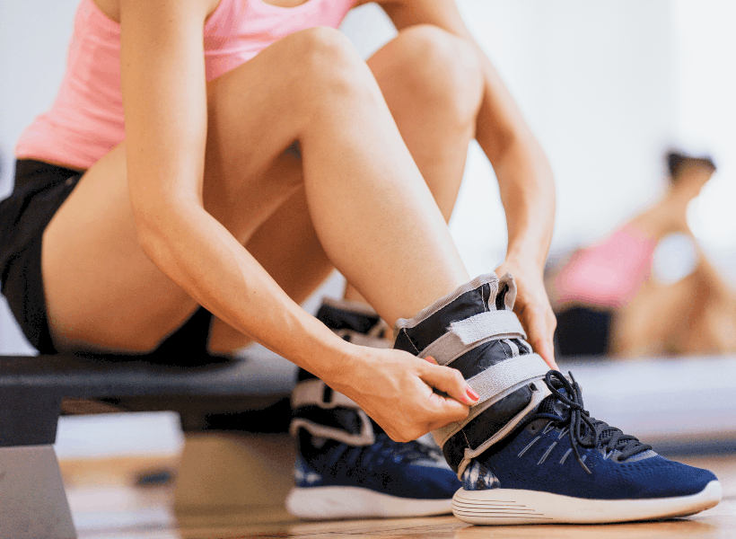 lady with shorts strapping ankle weights around ankle