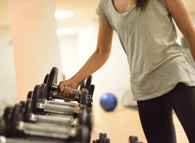 a thin lady taking a dumbbell from a rack of weights