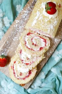 Slices of Strawberry Shortcake Roll Cake on a cutting board