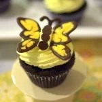 A close up of a dark chocolate butterfly cupcake on a cake stand