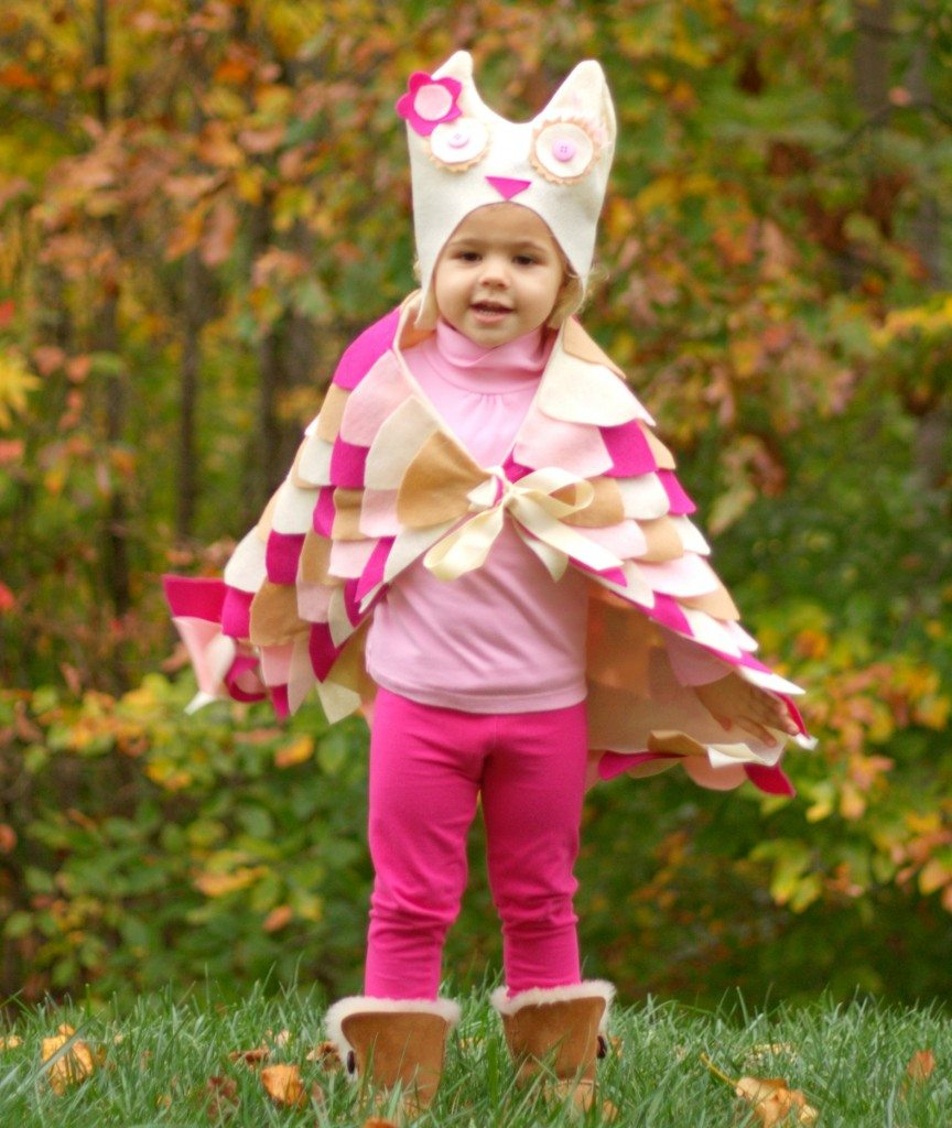 A little girl in a DIY pink owl costume
