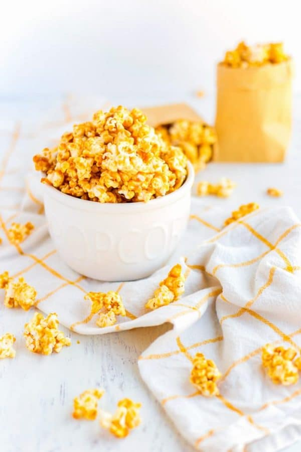 Caramel Corn in a white bowl and some pieces scattered on a tabletop.