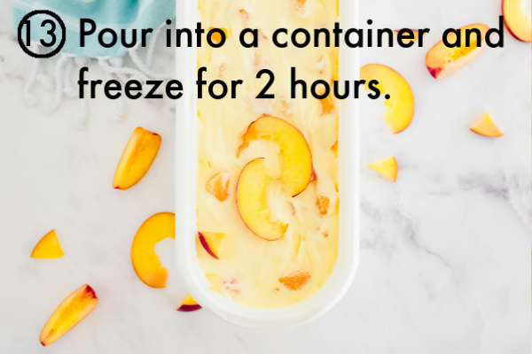 The ice cream inside an ice cream container that is garnished with fresh peaches.