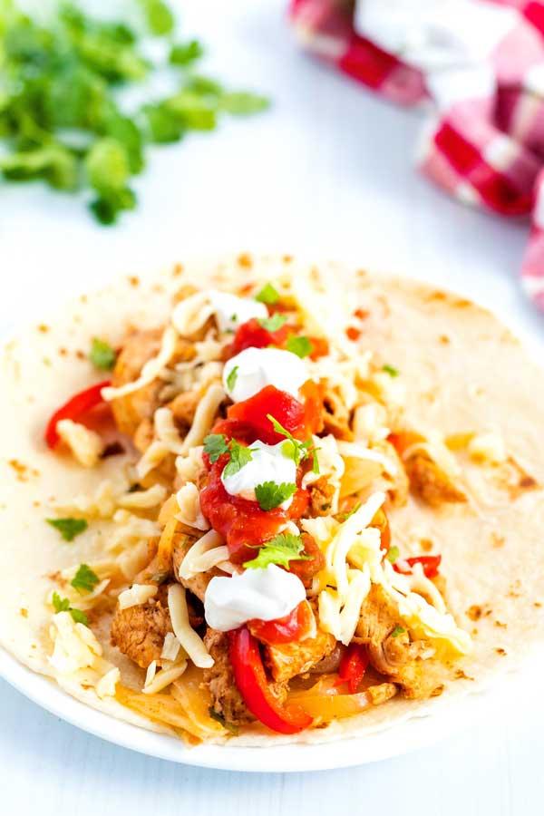 Chicken fajitas on a flour tortilla with sour cream, salsa, cheese, and cilantro.
