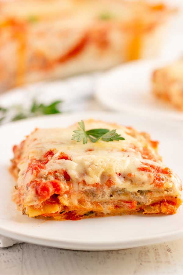 A slice of Lasagna with Italian Sausage on a white plate.