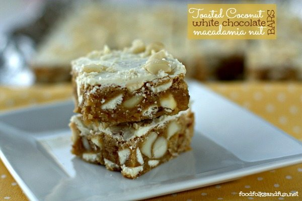 two pieces of white chocolate macadamia nut cookies stacked on a plate with text overlay for Pinterest