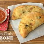 Two calzones on a table with text overlay for Pinterest