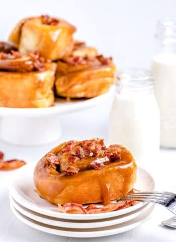 A glistening bacon sticky bun with caramel glaze on a white plate.
