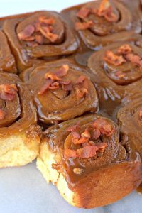 bacon sticky buns on a marble board.