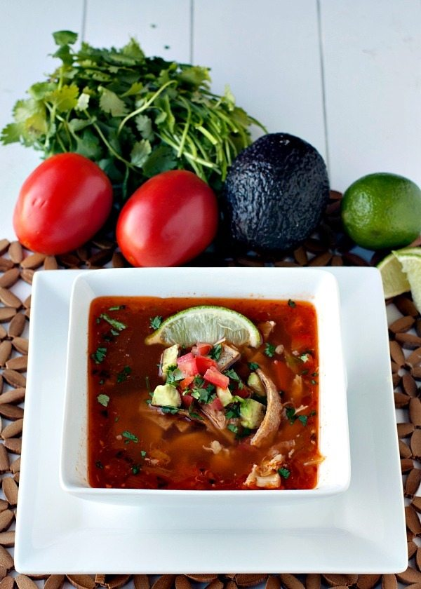 Chipotle Tortilla Soup in a white bowl surrounded by tomatoes, cilantro, avocados, and limes.