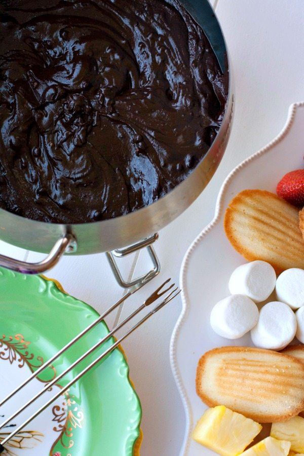 Chocolate fondue in a fondue pot with items to dip on a plate next to it