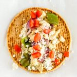 Place the chicken souvlaki mixture and toppings on the pita.