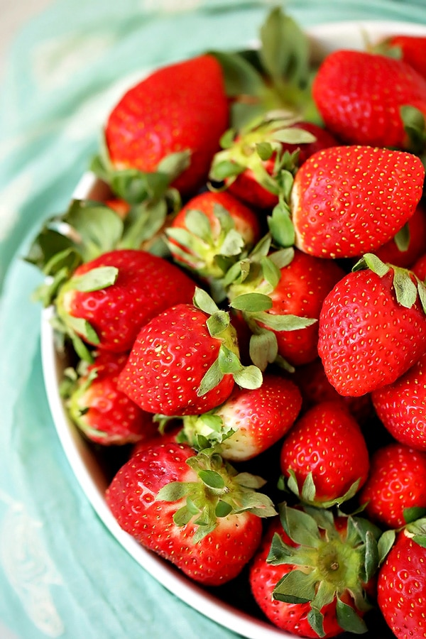 Close up picture of strawberries in a bowl with a blue cloth around it.