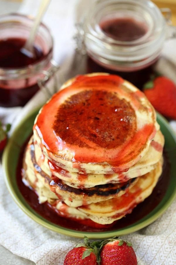 A large stack of pancakes with strawberry pancake syrup on them.