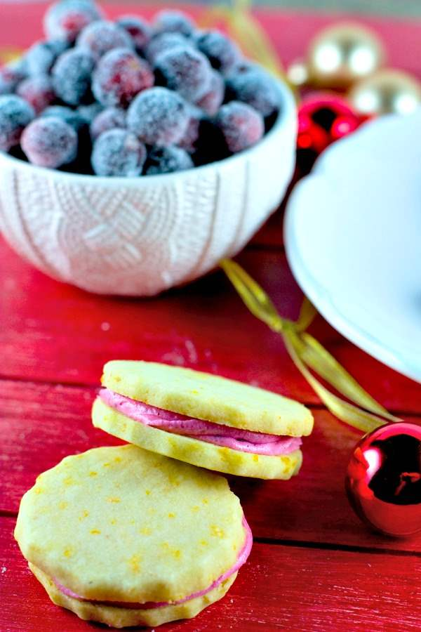 Orange shortbread sandwich cookies on a red table.