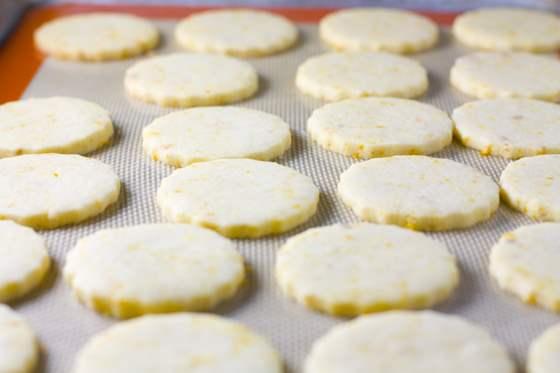 Orange shortbread cookies on a baking sheet.
