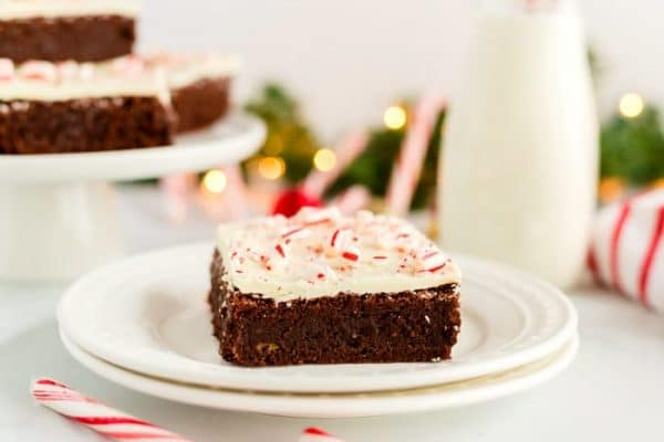 A brownie on a white plate with milk and candy canes in the background.