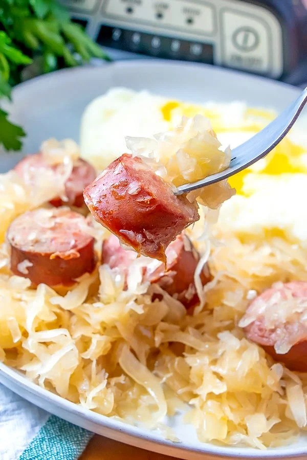 Serving kielbasa kapusta on a white plate.