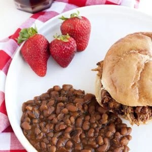 A plate full of Boston Baked Beans with some sandwiches and a Pulled Pork Sandwich.
