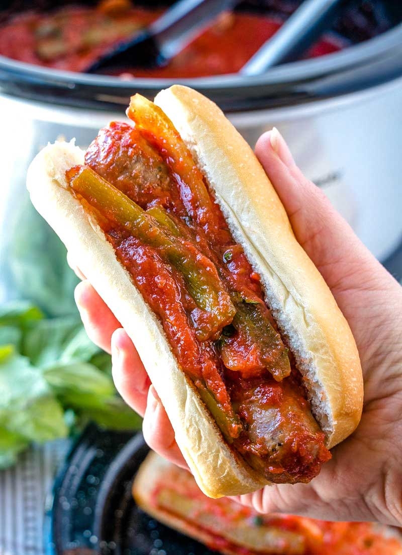 A hand picking up sausage and peppers on an Italian sub.