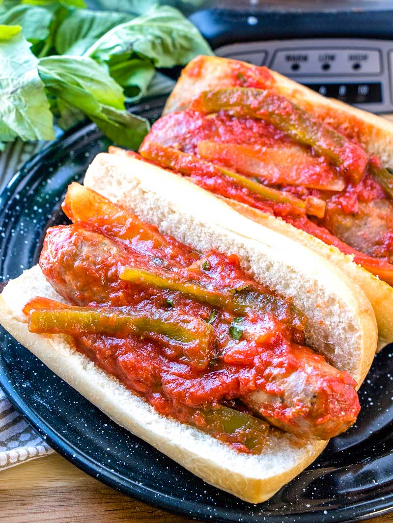 Two Sausage and Pepper subs on a black serving plate.