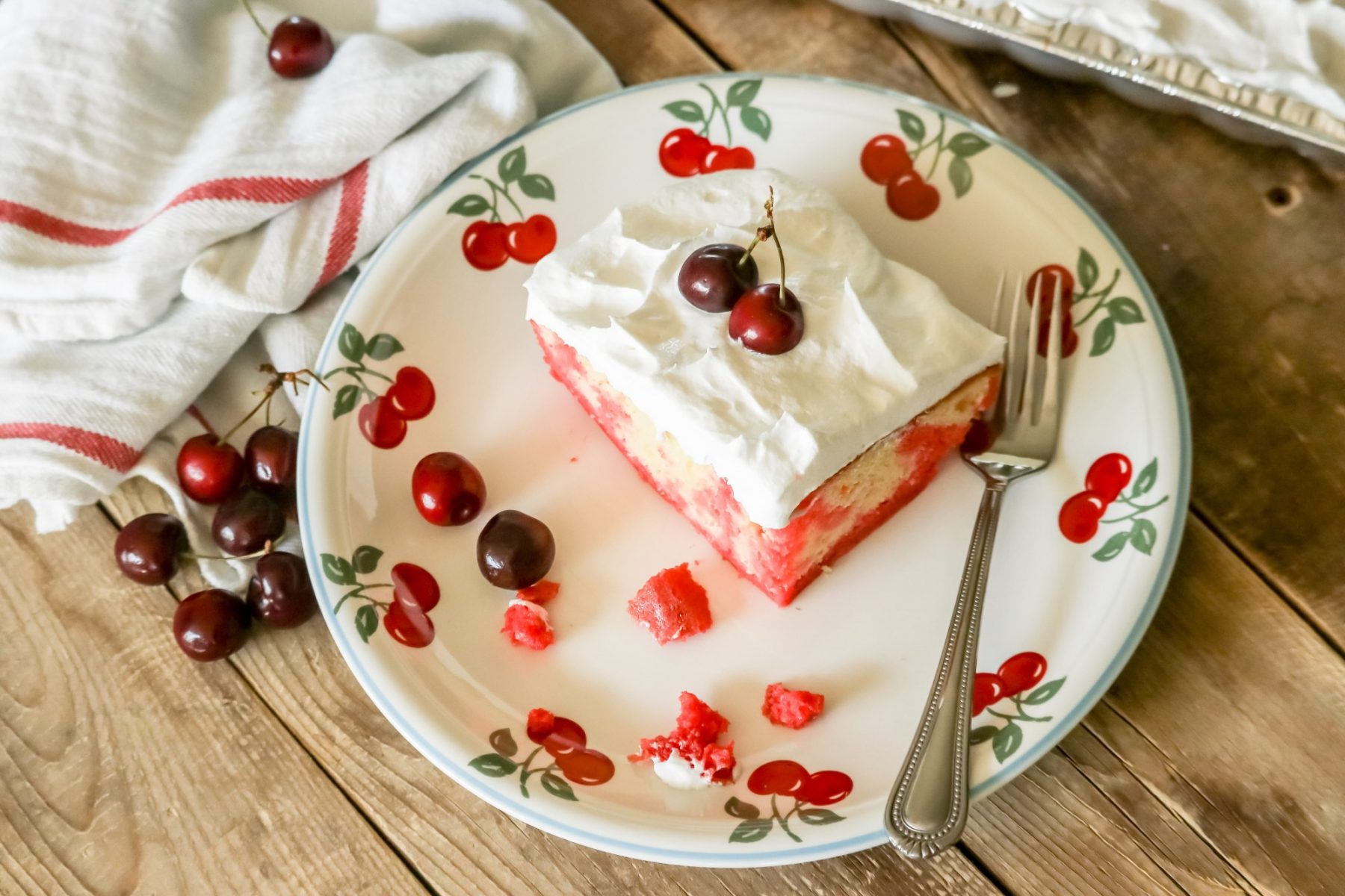 A slice of Cherry Jello Poke Cake on a plate