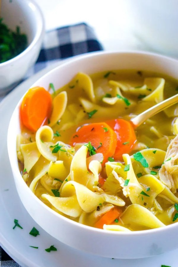 A close up of the BEST Rotisserie Chicken Noodle Soup recipe in a white bowl.