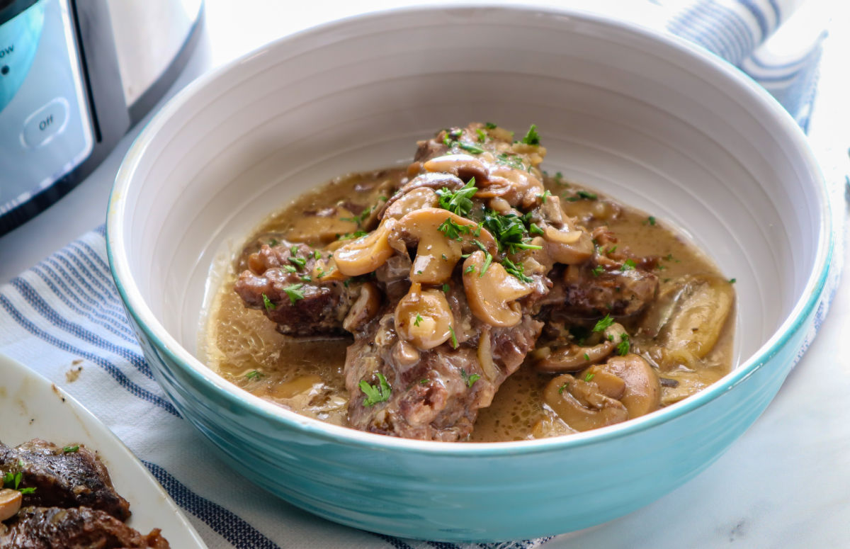 Slow cooker pot roast in a blue bowl smothered in a mushroom gravy.