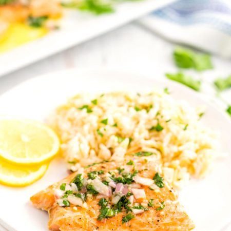 A baked salmon fillet on a white plate with rice pilaf and lemon slices.