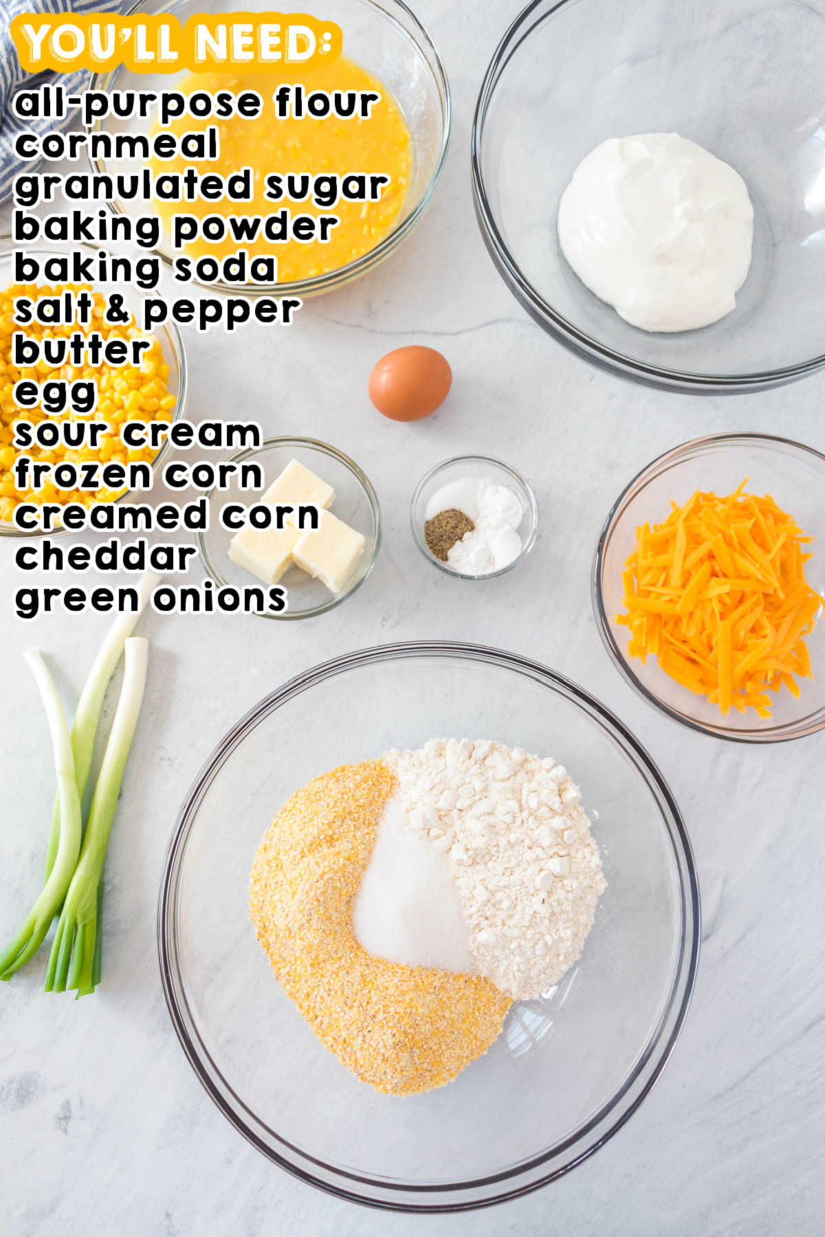 An overhead picture of all of the ingredients needed to make cornbread casserole.