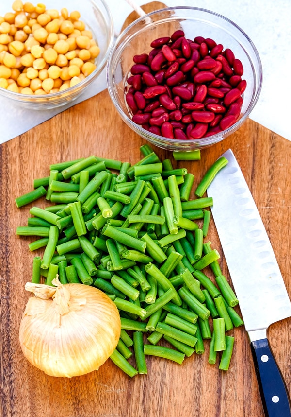 All of the ingredients needed to make 3 bean salad on a wooden cutting board.