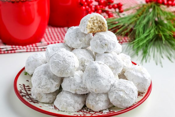 A plate full of pecan snowball cookies stacked on top of each other.