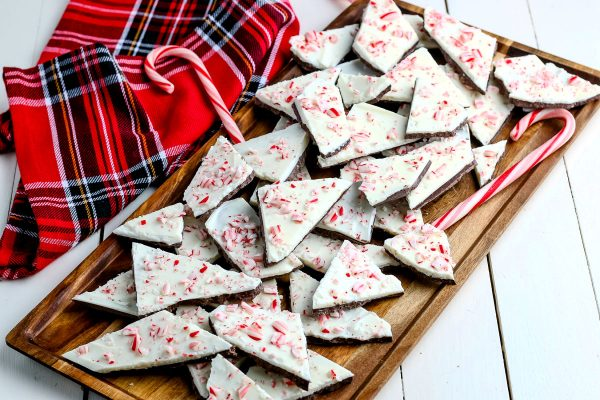 Peppermint bark on a serving tray with a plaid towel and candy canes in the background.