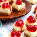 The finished Cheesecake Bars garnished with cherry pie filling.