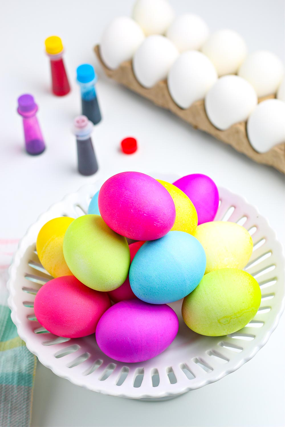 A picture of dyed Easter eggs with good coloring bottles in the background.