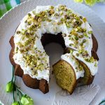 An overhead picture of Pistachio Bundt Cake that is made from scratch. Lemons and green and yellow flowers surround the cake.