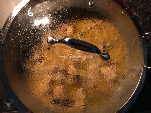 Simmering Bengali Posto recipe  in a kadhai with lid on