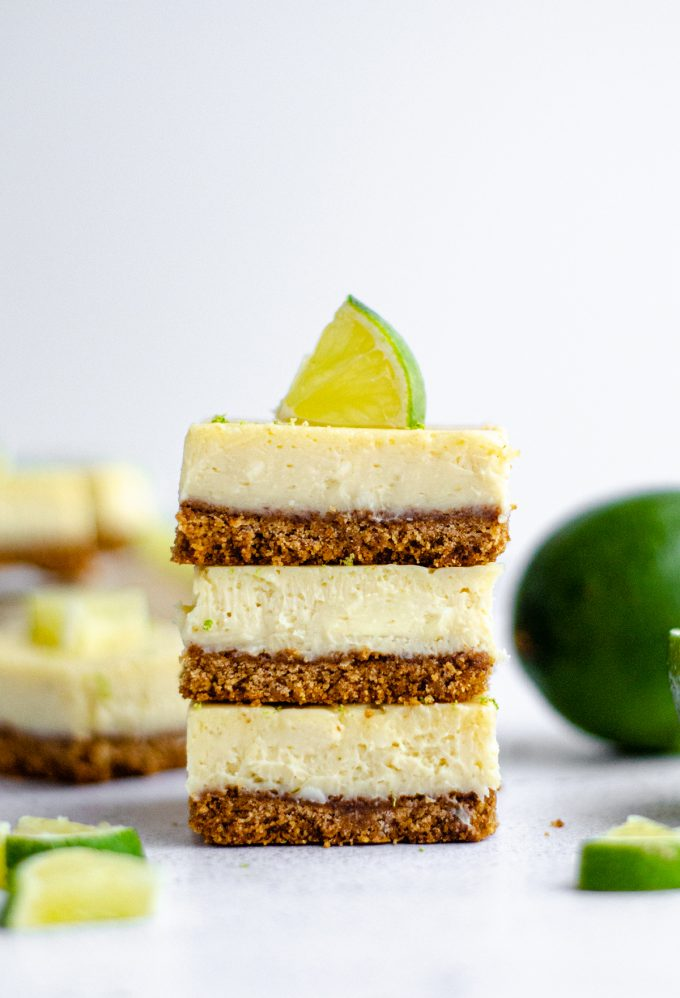 stack of key lime pie bars with slices of lime scattered around and on top of the stack